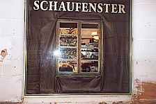 Blick von außen durch ein Fenster in eine Wohnstube bei der Ausstellung.