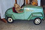 Ein Spielzeugauto zum Fahren mit einem Teddybären als Fahrer.