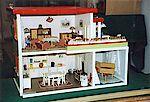 Ein Puppenhaus zweistöckig mit Küche, Wohnzimmer und Terrasse.