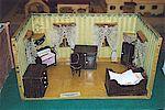 Ein Puppenhausschlafzimmer mit Bett und Kommode.