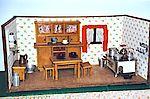 Eine Puppenhausküche mit Herd, Schrank, Tisch und Stühlen.