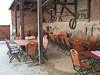 Die überdachten Außenanlagen der Remise mit Tischen und Stühlen.